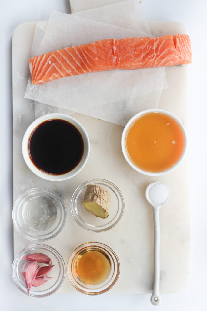 Picture of ingredients used in recipe, salmon fillet, ginger, garlic cloves, soy sauce, honey, salt, sesame seed oil and mirin