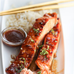 Picture of salmon that has been garnished with sesame seeds and spring onion accompanied with rice